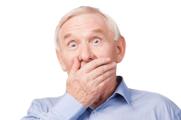 Certainement pas! excité senior homme formalwear couvrant la bouche avec la main et regardant la caméra en se tenant debout sur fond blanc