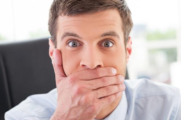 Certainement pas! jeune homme choqué en tenue de soirée couvrant la bouche avec la main et regardant la caméra alors qu'il était assis sur son lieu de travail