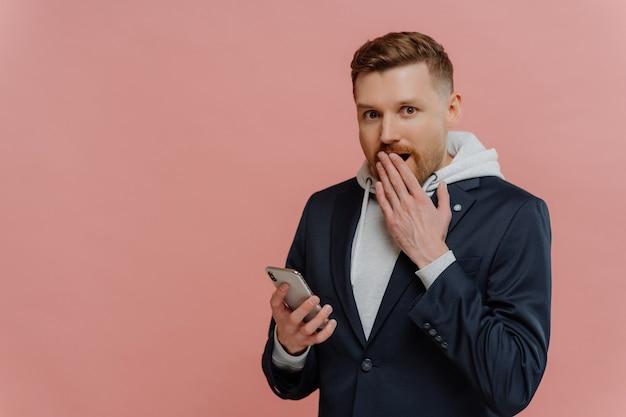 Certainement pas. jeune homme étonné aux cheveux rouges en tenue décontractée regardant la caméra avec une expression abasourdie, lisant des nouvelles inattendues sur un smartphone tout en se tenant isolé sur fond rose pastel