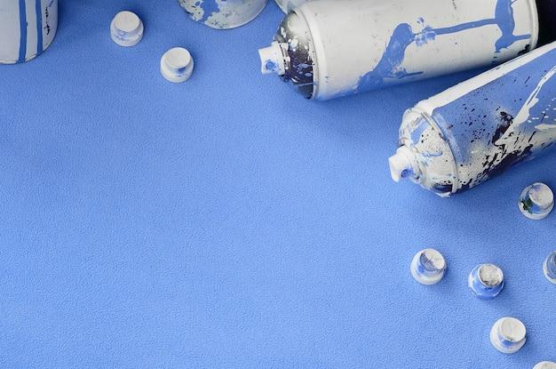 Certaines bombes aérosol bleues utilisées et des buses avec des gouttes de peinture se trouvent