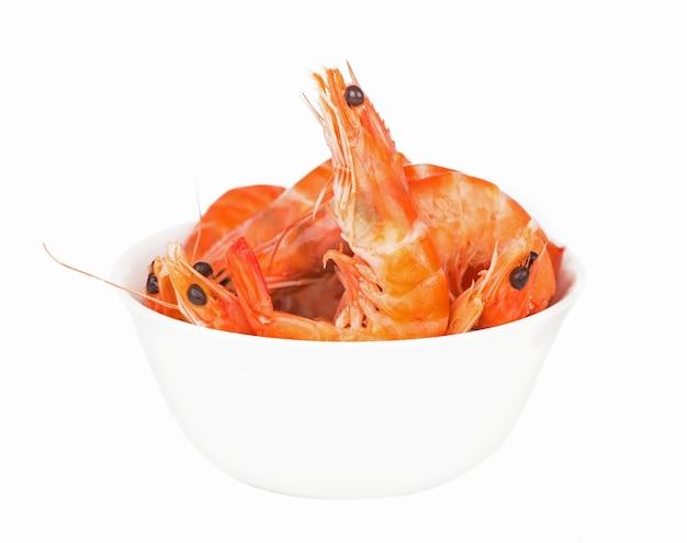 Certaines crevettes dans un plat blanc fruits de mer isolé sur mur blanc