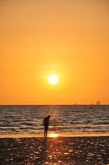 Certaines personnes sont sur une plage au coucher du soleil