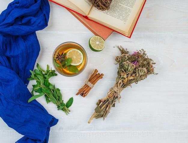 Certaines tisanes et fleurs avec des livres, du citron, des épices et un foulard bleu sur une surface blanche
