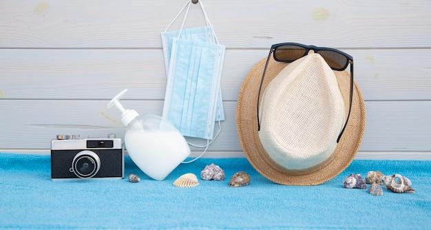 Certains accessoires de plage ainsi que des articles de protection contre les coronavirus placés sur une planche de bois.