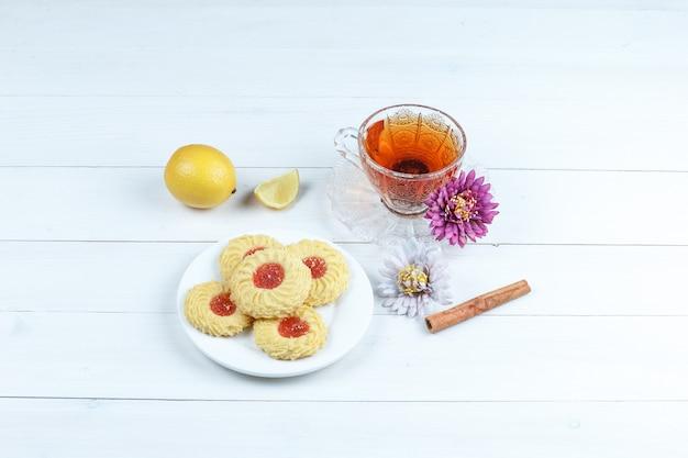 Certains cookies, tasse de thé à la cannelle, citron, fleurs sur fond de planche de bois blanc, vue grand angle.