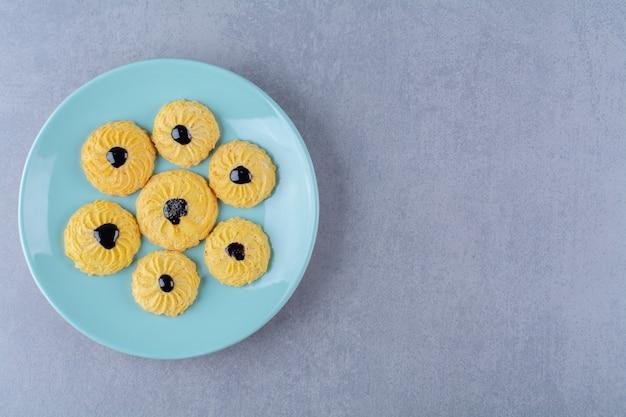 Certains de délicieux biscuits jaunes avec du sirop de chocolat sur une plaque bleue.