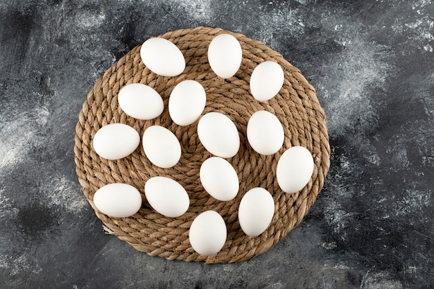 Certains œufs de poule crus blancs sur un sac.