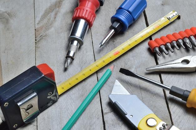 Certains outils de réparation à domicile se trouvent sur un fond en bois. fermer.