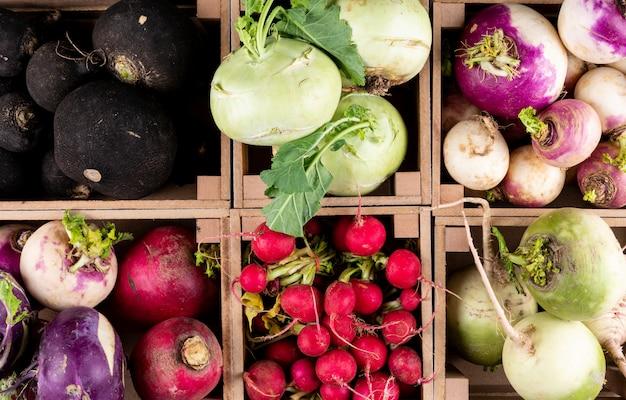 Certains de radis frais rouges, noirs, blancs et différents dans une vue de dessus de caisse de fermier en bois.