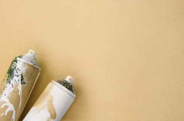 Certains vaporisateurs orange en aérosol avec des gouttes de peinture se trouvent sur une couverture