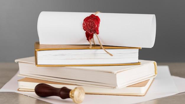 Certificat avec cachet de cire sur une pile de livres vue de face