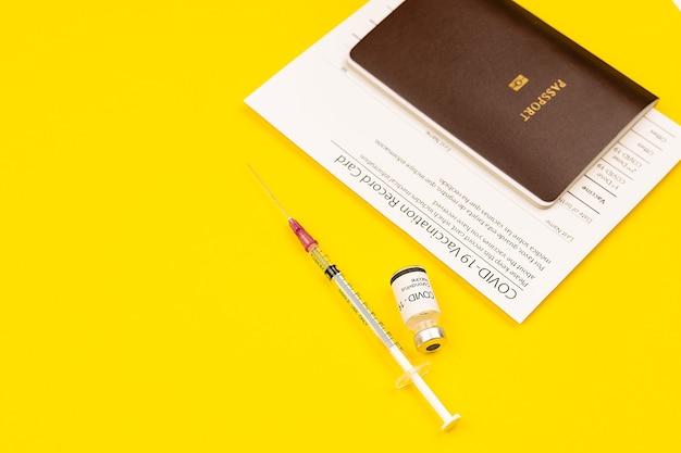 Certificat de carte d'enregistrement vacciné covid-19 et passeport avec bouteille et seringue de vaccin contre le coronavirus assemblés sur fond jaune avec espace de copie.