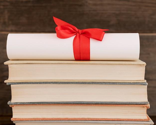 Certificat de diplôme d'éducation sur une pile de livres