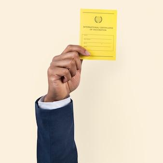 Certificat de vaccin covid-19 tenu par la main d'un homme d'affaires