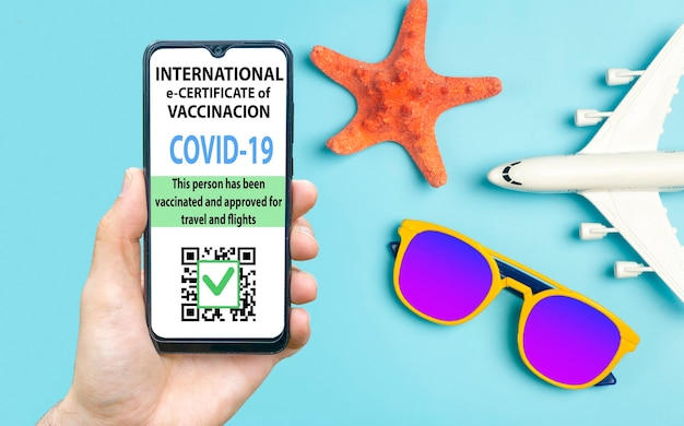 Certificat de vaccination contre le coronavirus ou passeport de vaccin pour le concept de voyageurs. passeport électronique d'immunité covid-19 dans l'application mobile pour smartphone pour les voyages internationaux. fond bleu avec des lunettes de soleil,