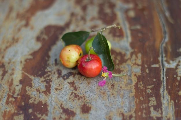 Certifié biologique brésilienne acerola fruit petite cerise sur planche de bois.