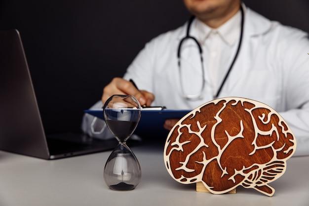 Cerveau en bois et sablier dans le bureau des médecins l'importance du concept de diagnostic précoce