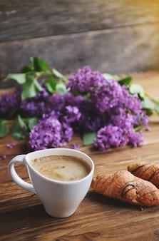 Cet printemps et petit-déjeuner frais sur une table en bois. des croissants sereins et une tasse à cappuccino sont sur la table. un bouquet de lilas sur une table en bois.
