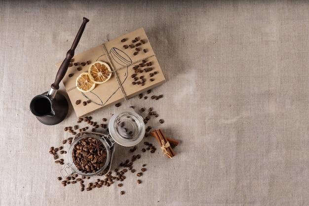 Cezve et grains de café torréfiés en boîte sur une table rustique, cannelle et citron séché.