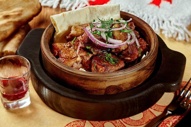 Chachlik de porc grillé sur lavash avec oignons frais et verdure