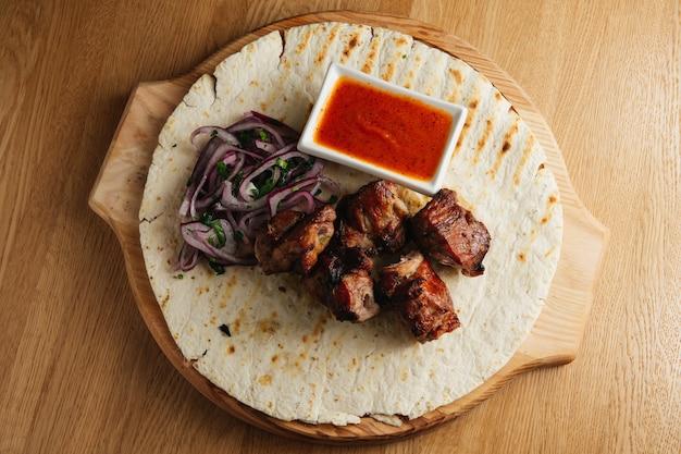 Chachlik traditionnel russe sur une brochette de barbecue avec oignon, lavash et sauce sur planche de bois