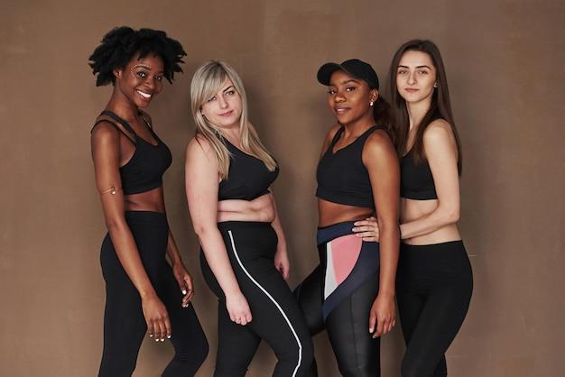 Chacun est beau à sa manière. groupe de femmes multiethniques debout contre l'espace brun