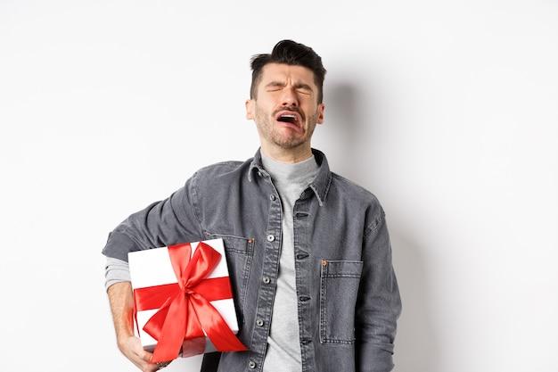 Le chagrin de la saint-valentin. un gars célibataire et navré pleurant seul, tenant une grande boîte cadeau, rejeté par son amant, sanglotant et se sentant seul, debout sur blanc.