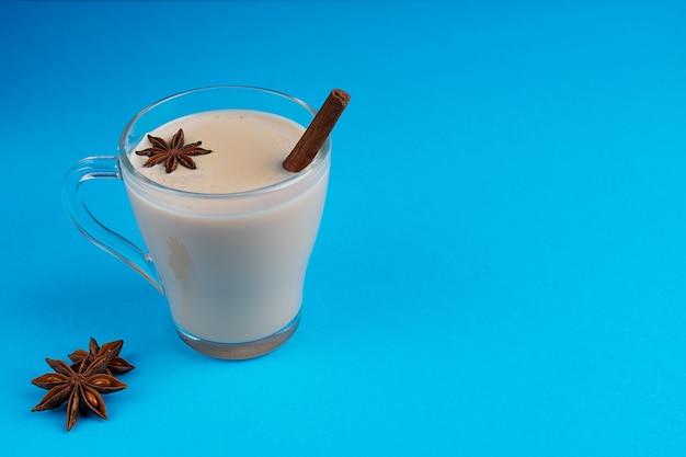 Chai masala chaud ou thé aux épices mélangées à base de lait, d'anis et de cannelle sur bleu