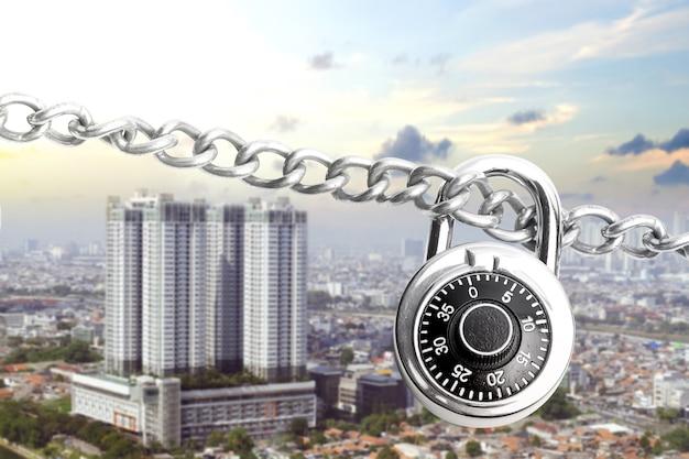 Chaîne d'acier métallique avec cadenas et paysage urbain avec un fond de ciel bleu