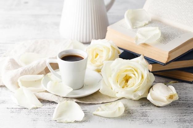 Chaîne de boire du café chaud sur un plancher en bois avec de belles roses.