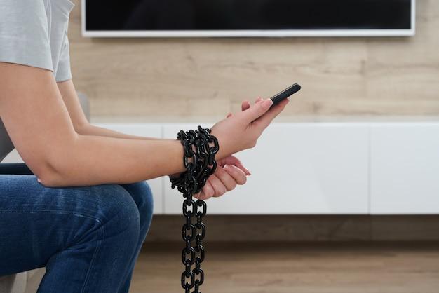 Chaîne de fer qui relie la main et le smartphone dans le concept de dépendance aux médias sociaux et à internet
