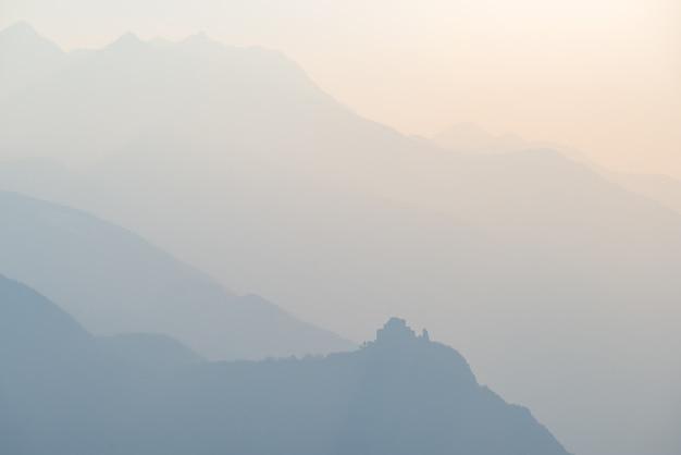 Chaîne de montagne lointaine aux tons bleus avec le profil de l'abbaye de saint-michel au bas.
