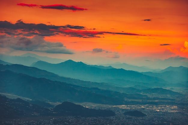 Chaîne de montagnes bleues et coucher de soleil orange ciel nuageux