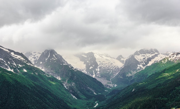 Chaîne de montagnes du dombay dans le caucase en été, sommets enneigés et pentes de montagnes verdoyantes