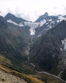 Chaîne de montagnes enneigées dans les nuages. vallée avec un ruisseau de montagne. caucase, russie