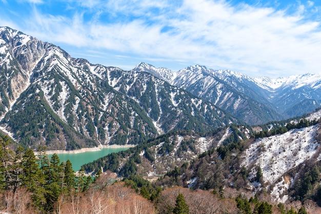 Chaîne de montagnes enneigées et lac kurobe sur la route alpine tateyama kurobe.