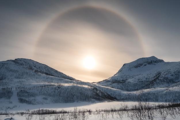 Chaîne de montagnes de neige avec halo de soleil en hiver au matin