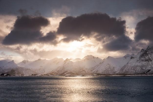 Chaîne de montagnes de neige avec nuageux et la lumière du soleil brille sur le littoral