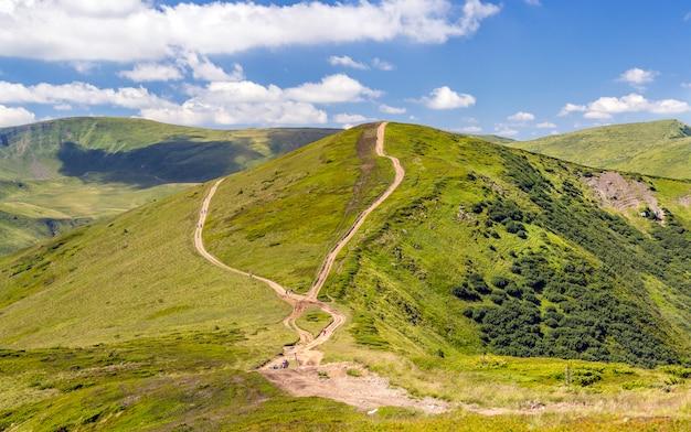 Chaîne de montagnes avec route de gravier et randonneurs. montagnes des carpates en ukraine en été