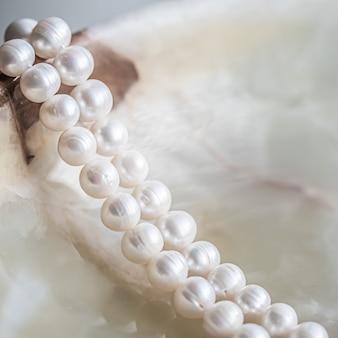 Chaîne de perles blanches nature sur fond de marbre en flou avec des reflets