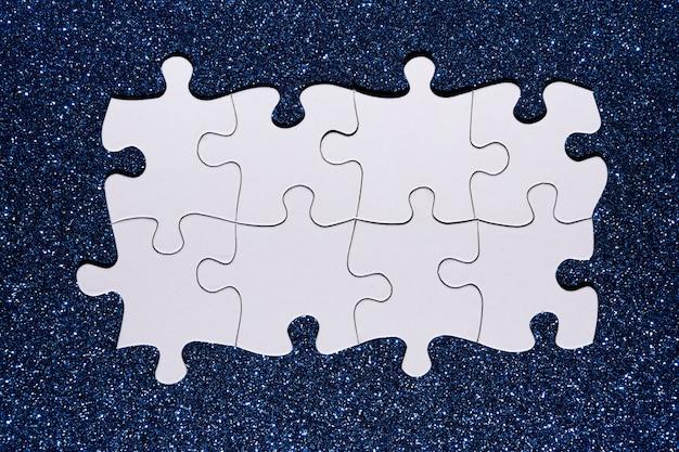 Chaîne de puzzle blanc sur fond de paillettes bleues