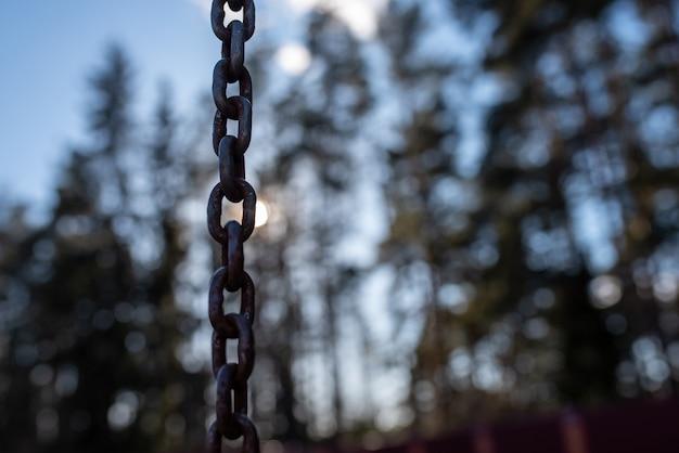 Une chaîne rouillée au milieu du soleil et du ciel. à toutes fins utiles.