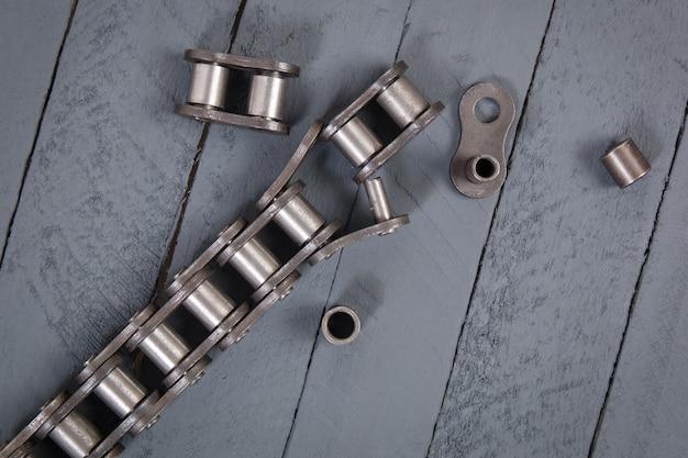 Chaîne à rouleaux d'entraînement cassée. parties de la chaîne industrielle détruite