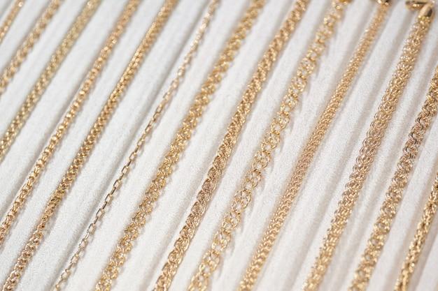 Chaînes et bijoux en or sur un comptoir blanc.