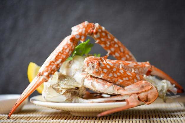 Chair de crabe - pinces et pattes de crabe cuit sur plaque blanche et sauce aux fruits de mer sur la table, crabe bleu nageant