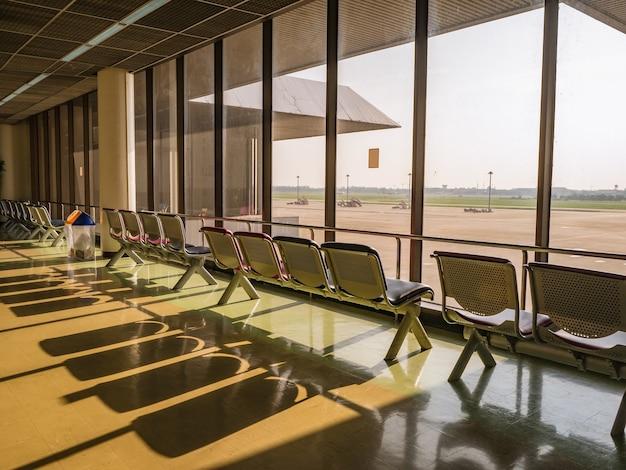 Chaise de l'aéroport à côté de la fenêtre le matin à l'aéroport international don muang de bangkok city
