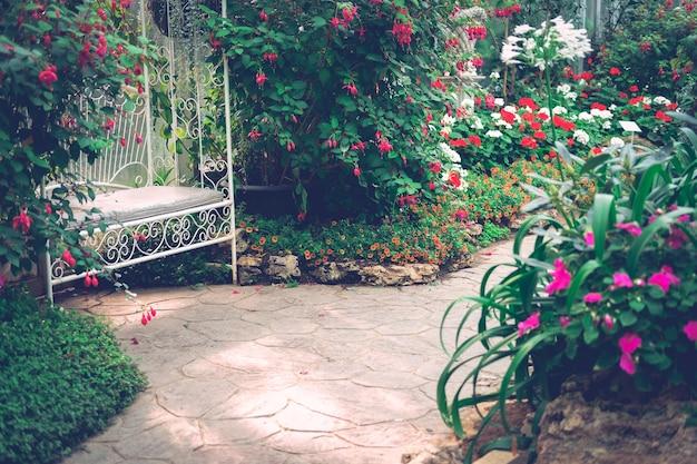 Chaise assise en métal blanc dans le parc de jardin fleuri au printemps été
