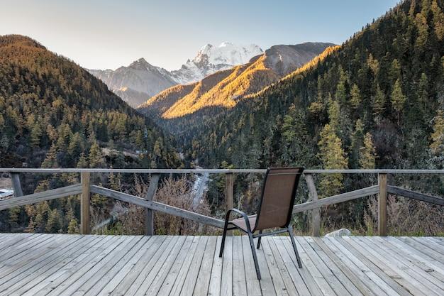 Chaise sur un balcon en bois avec vallée en automne au soir