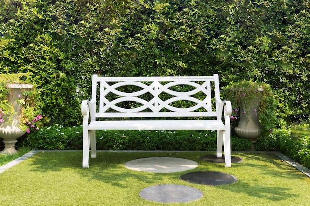 Chaise de banc en bois blanc avec buisson fond dans le jardin à la maison.