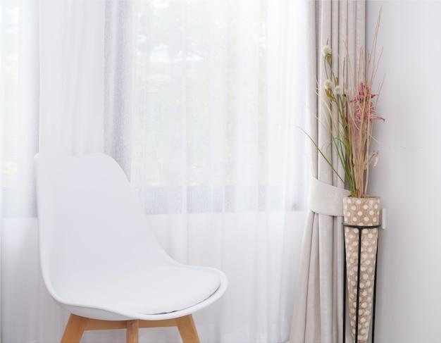 Chaise blanche moderne située dans un salon blanc avec une fleur séchée et un intérieur de rideau pastel doux